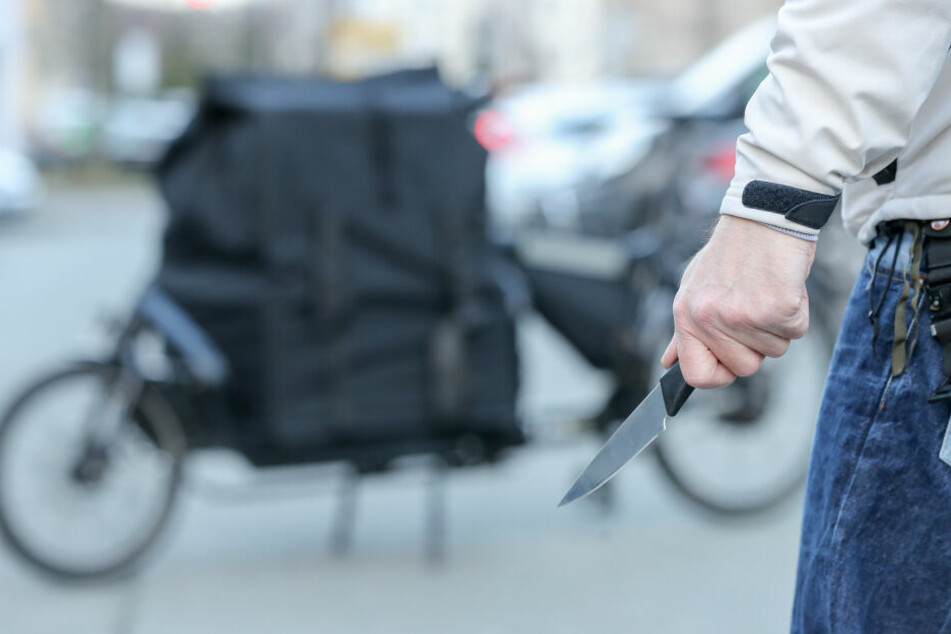 Ein Mann steht mit einem Messer in der Hand (Symbolbild).