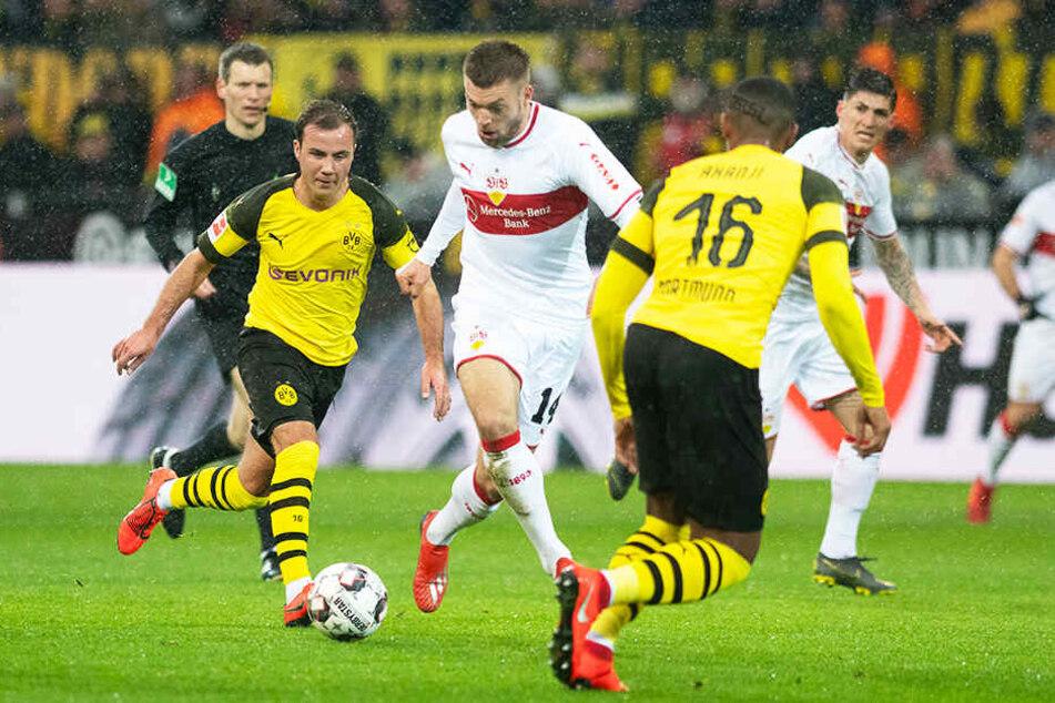 Die Dortmunder Mario Götze (l.) und Manuel Aknaji (r.) versuchen, VfB-Angreifer Alexander Esswein (M.) vom Ball zu trennen.