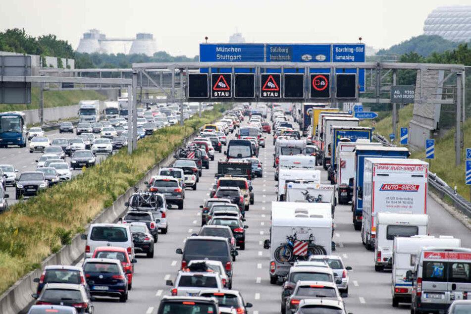 Zähfließender Verkehr herrscht auf der Autobahn A9 bei München, während auf einer Anzeigetafel über der Autobahn vor Stau gewarnt wird.