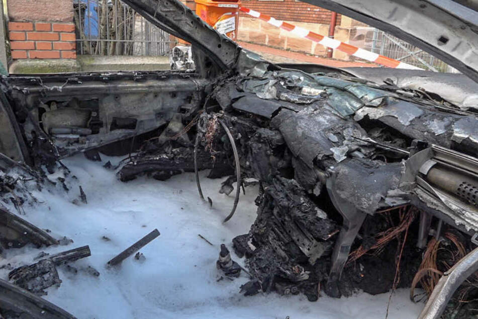 Ein ausgebranntes Fahrzeug steht auf einer Straße. Ein neunjähriger Bub hat seine zweijährige Schwester aus diesem brennenden Auto gerettet.