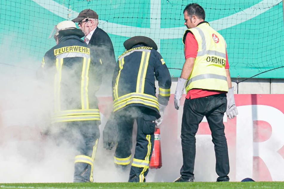 Feuerwehrleute löschen am 10.08.2019 beim Spiel gegen Kaiserslautern brennende Bengalos, die von Mainzer Fans aufs Spielfeld geworfen wurden.