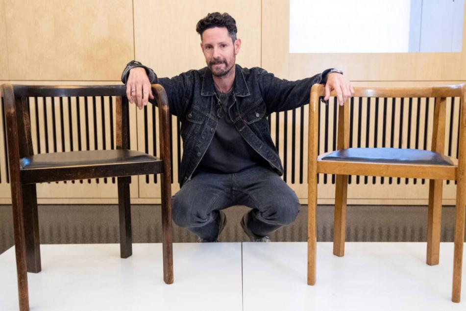 HipHop-Musiker Max Herre kniet neben zwei Stühlen.