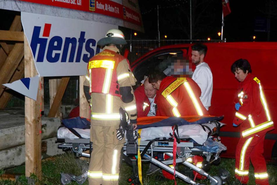Die Rettungskräfte holen den verletzten Mann aus dem Wagen.