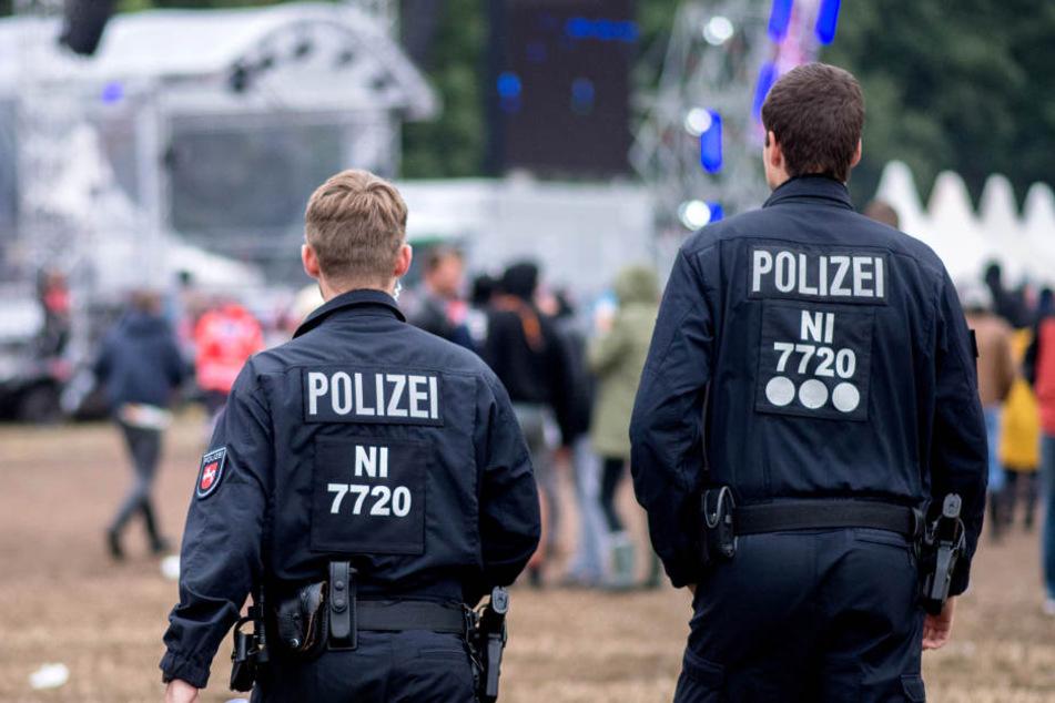 Zwei Polizisten überwachen ein Festivalgelände. (Symbolbild)
