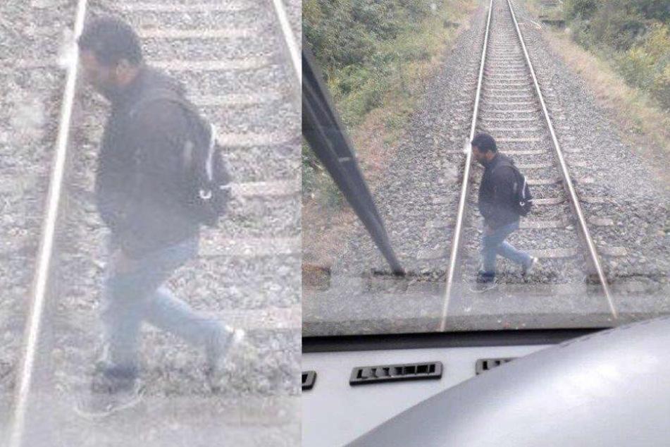 Mann spaziert auf den Gleisen, dann rauscht ein Zug heran