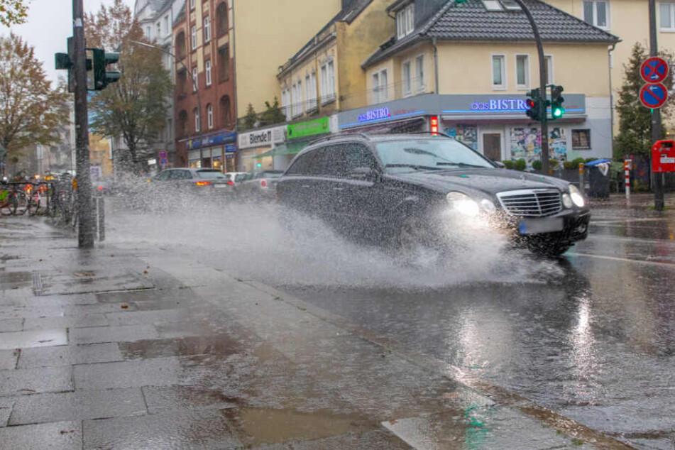 Ein Auto fährt durch eine große Pfütze und spritzt das Wasser auf.