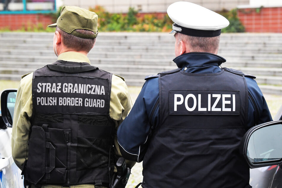 Ein Beamter der Bundespolizei (r.) und ein polnischer Grenzschützer stehen an der deutsch-polnischen Grenze. (Symbolbild)