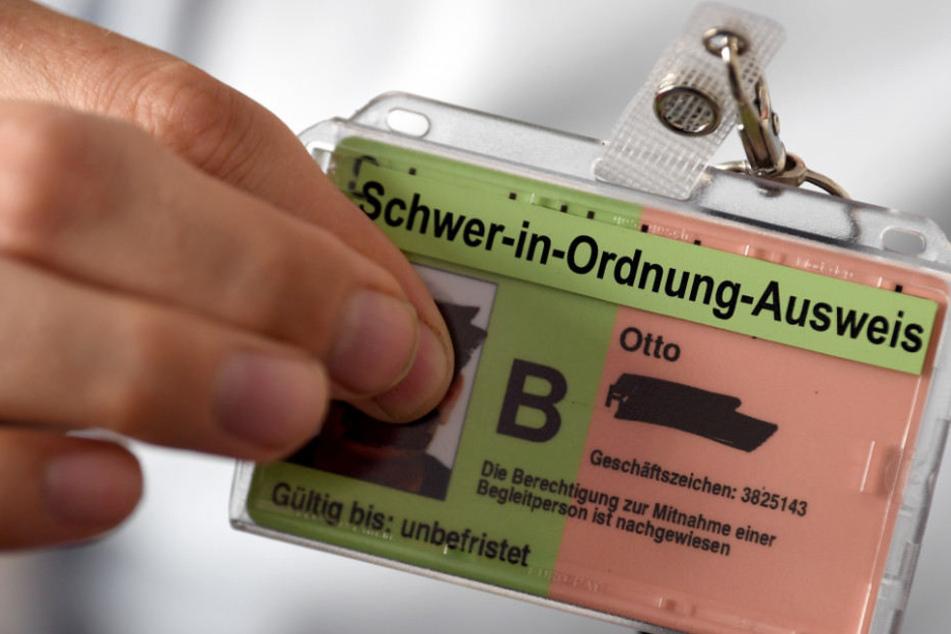 in junger Mann zeigt seine neue Hülle für seinen Schwerbehindertenausweis.