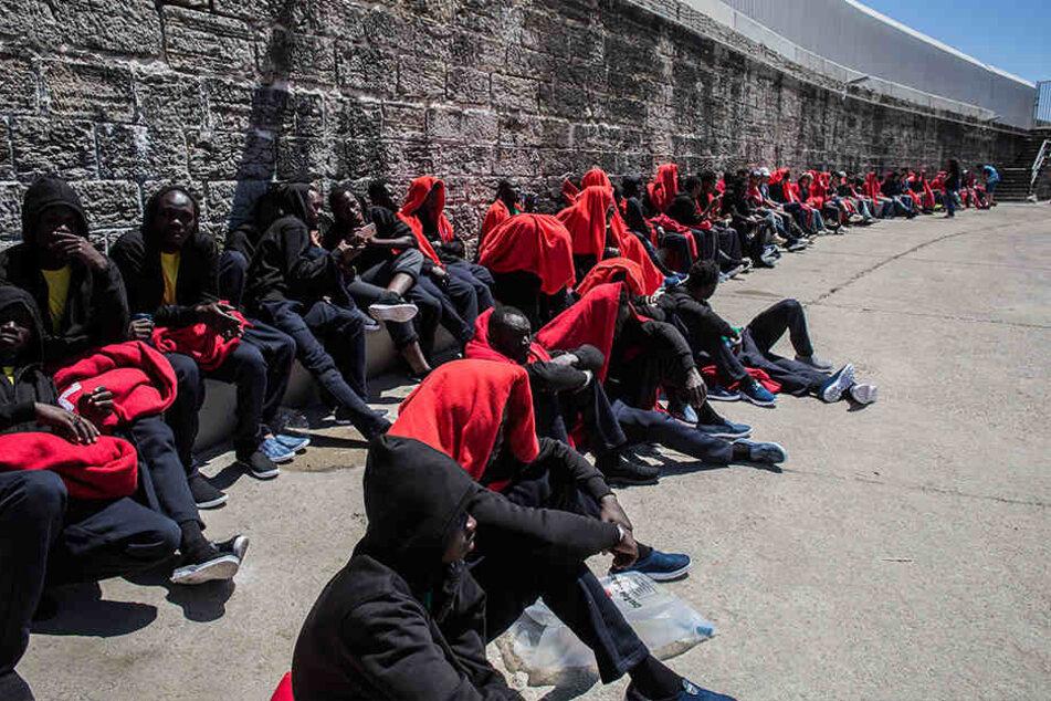 Migranten aus Afrika sitzen nach ihrer Rettung in der Straße von Gibraltar im Hafen von Tarifa in Decken gehüllt an einer Mauer.
