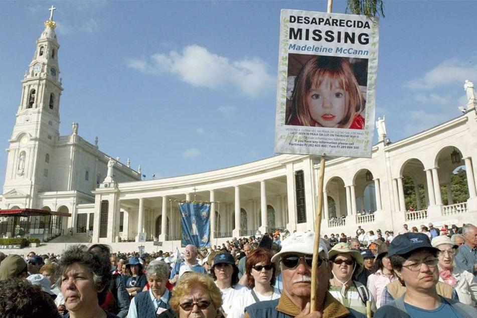 Gläubige halten am 12. Mai 2007 in Fatima (Portugal) ein Bild von Madeleine McCann in der Hand. Vor zehn Jahren, am 03. Mai 2007, verschwand Maddie in Portugal. Bis heute ist der Fall nicht aufgeklärt.