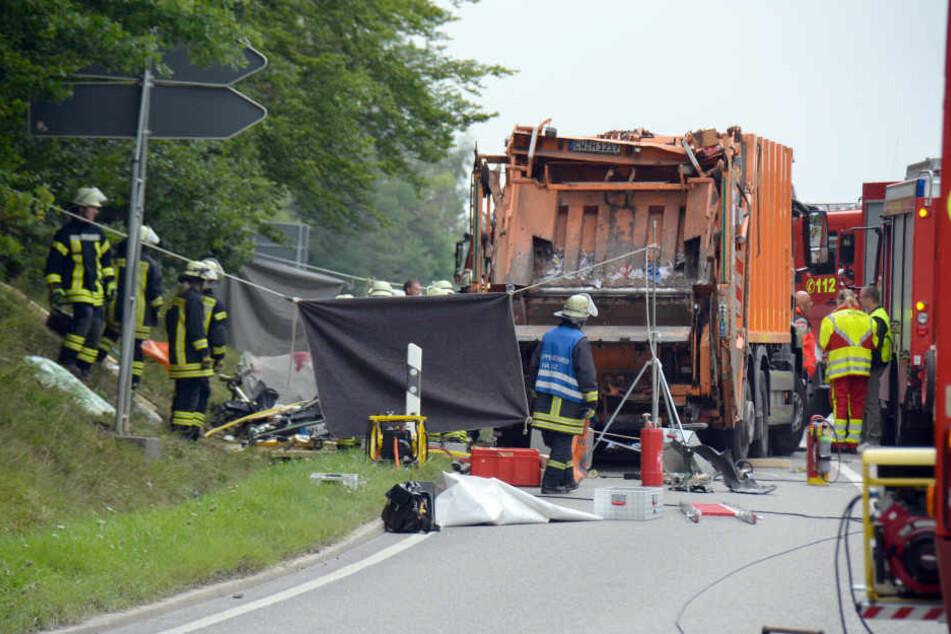 Feuerwehrkräfte arbeiten auf einer Straße bei Nagold an einer Unfallstelle, an der ein Müllwagen auf ein Auto gekippt war. Nach ersten Angaben der Polizei sind bei dem Unfall fünf Menschen ums Leben gekommen. (Archivbild)