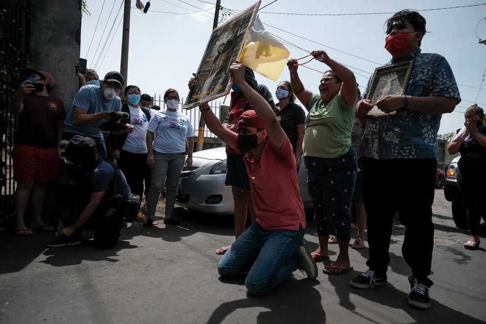 Katholische Gläubige mit Mundschutzmasken knien und trauern, nachdem ein Mann eine Brandflasche gegen die Kathedrale geworfen hat.