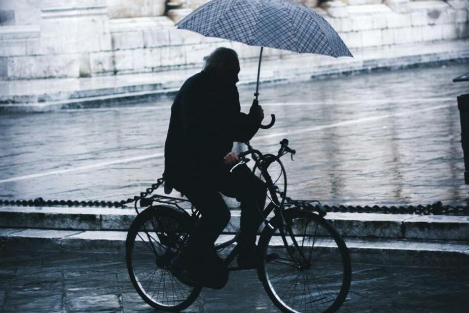 Bei schlechtem Wetter ist passende Radfahrer-Überbekleidung sinnvoller als ein Regenschirm. Auch für Profis heißt es sowieso immer: Beide Hände am Lenker.
