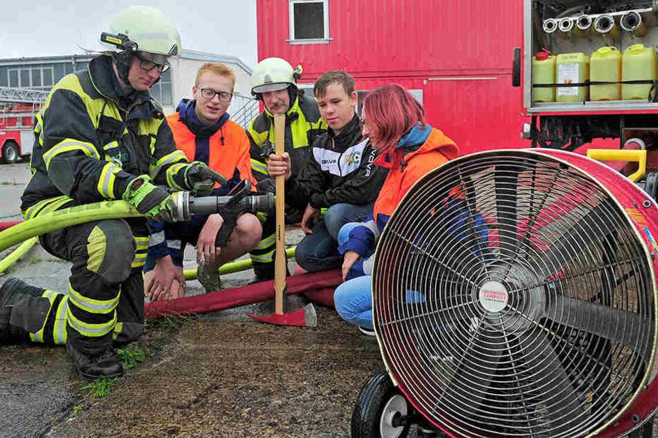 Feuerwehrmann Julian Schubert (18, l.) erklärt die Funktion der Spritzdüse am Feuerwehrschlauch.