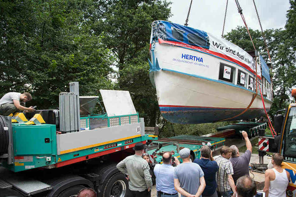 """Zwei Kräne verladen das am Ufer des Klempowsees auf Dock liegende Schiff """"Hertha""""."""