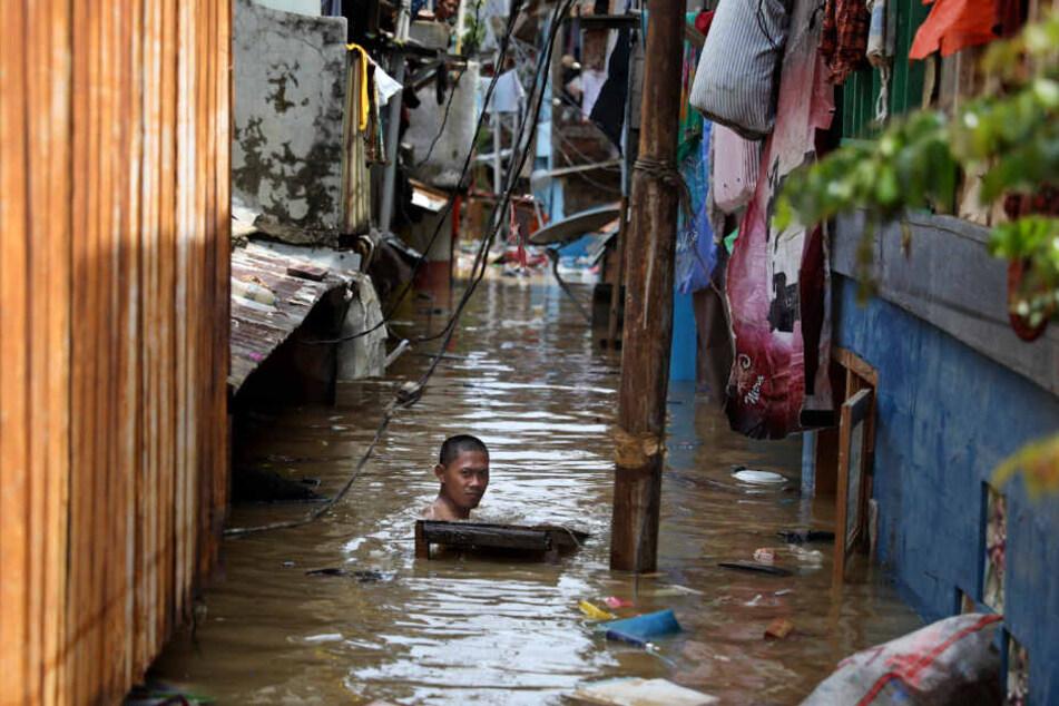 Ein Mann schwimmt durch das Hochwasser einer überfluteten Straße in seiner Nachbarschaft.