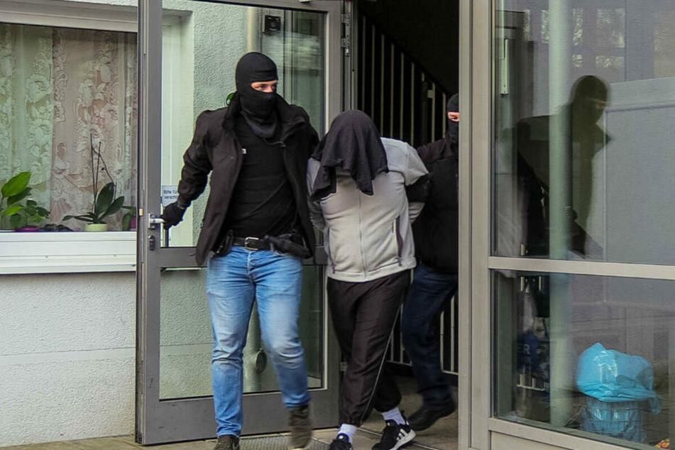 Der Tatverdächtige wird von zwei vermummten Beamten aus dem Haus geführt. (Archivbild)