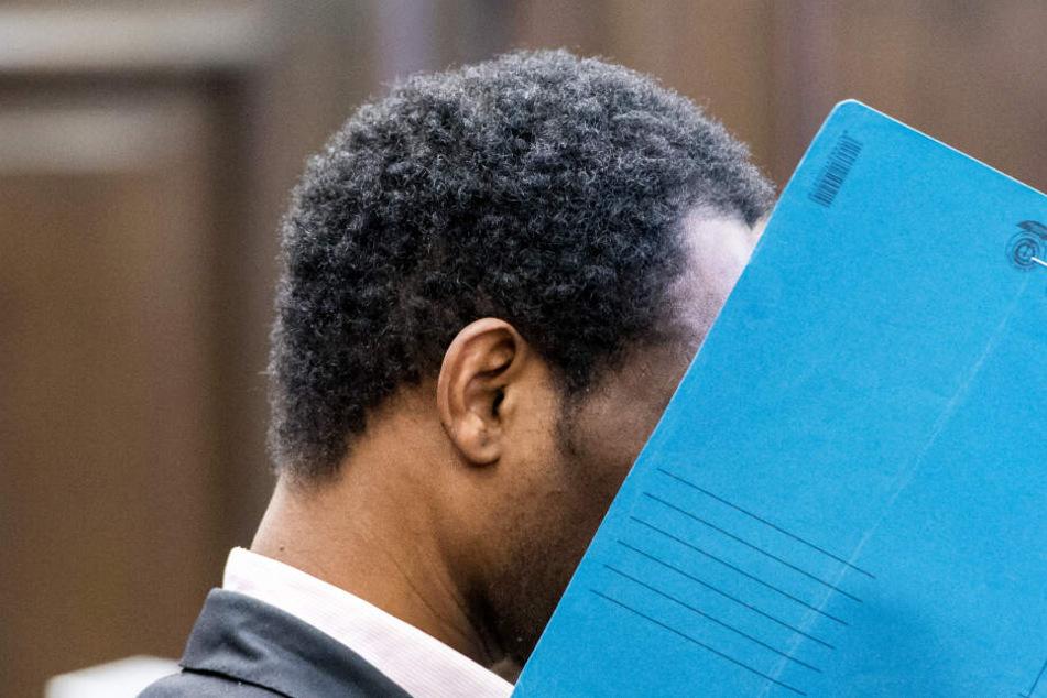 Mado Bido M. versteckt sein Gesicht vor Beginn der Urteilsverkündung hinter einer Mappe.