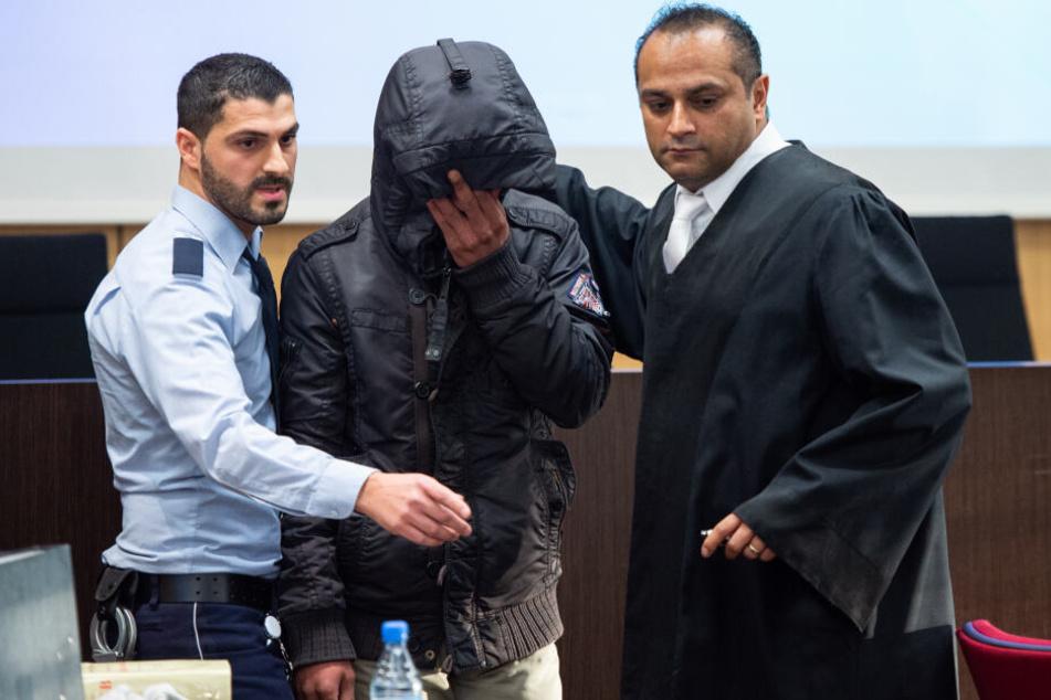 Der angeklagte Familienvater wird von einem Justizbeamten und einem seiner Verteidiger, in einen Saal im Land- und Amtsgericht Düsseldorf geführt.