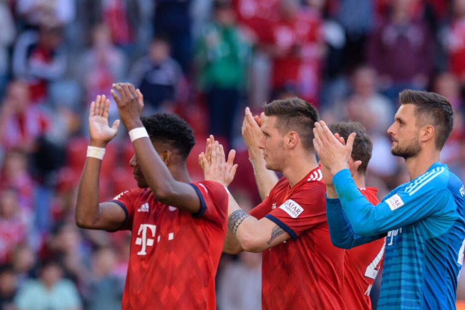 David Alaba (l-r), Niklas Süle und Sven Ulreich vom FC Bayern München feiern ihren Sieg gegen Bremen mit den Fans.
