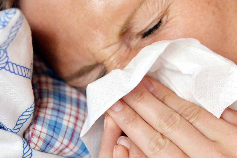 Eine Frau liegt im Bett und putzt sich die Nase. (Symbolbild)