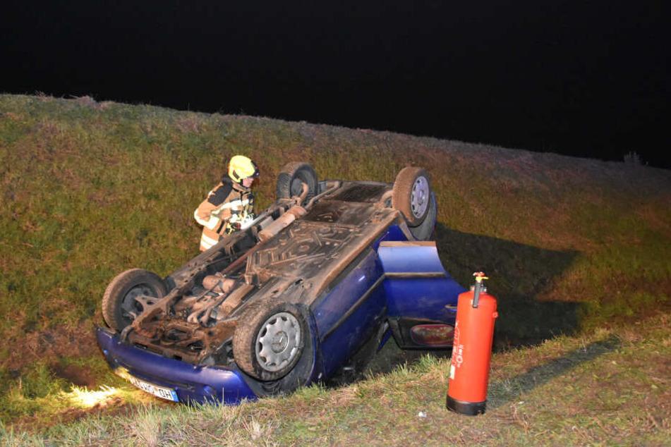 Ein Feuerwehrmann wirft ein Blick auf den verunfallten Wagen.