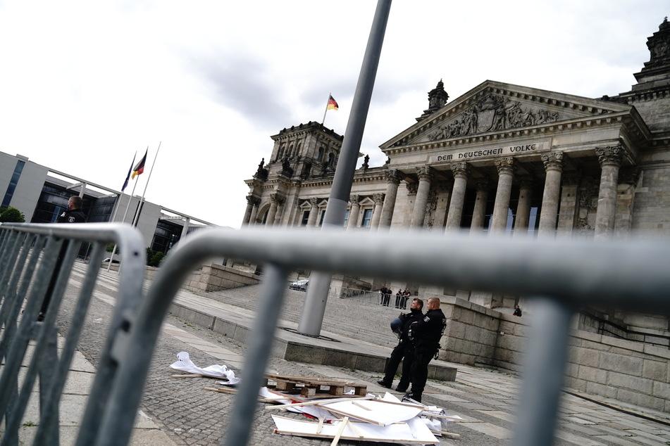 Polizeibeamte sichern hinter Absperrzäunen das Reichstagsgebäude.
