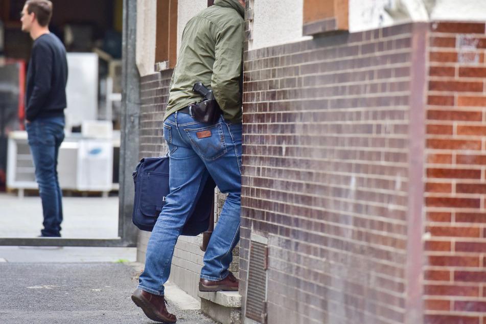 Ein Polizeibeamter betritt ein Haus in Bonn. Im Fall von zwei in einem Supermarkt schwer verletzten Polizisten sind am 13.Mai die Wohnungen von zwei Verdächtigen in Bonn und Troisdorf durchsucht worden.