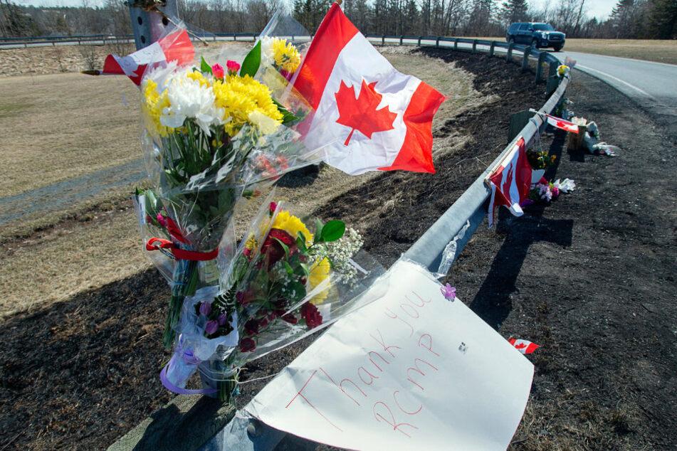 """Blumen, kanadischen Fahnen und ein Blatt Papier mit der Aufschrift """"Danke Royal Canadian Mounted Police (RCMP)"""" zieren eine Gedenkstätte."""