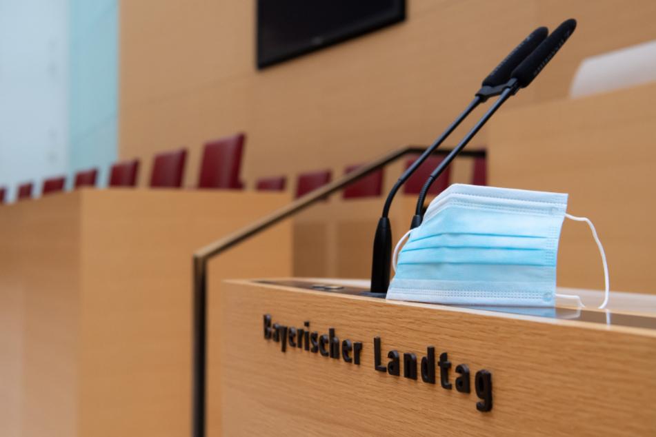 Ein Mund-Nase-Schutz befindet sich im Plenarsaal im bayerischen Landtag neben Mikrofonen.