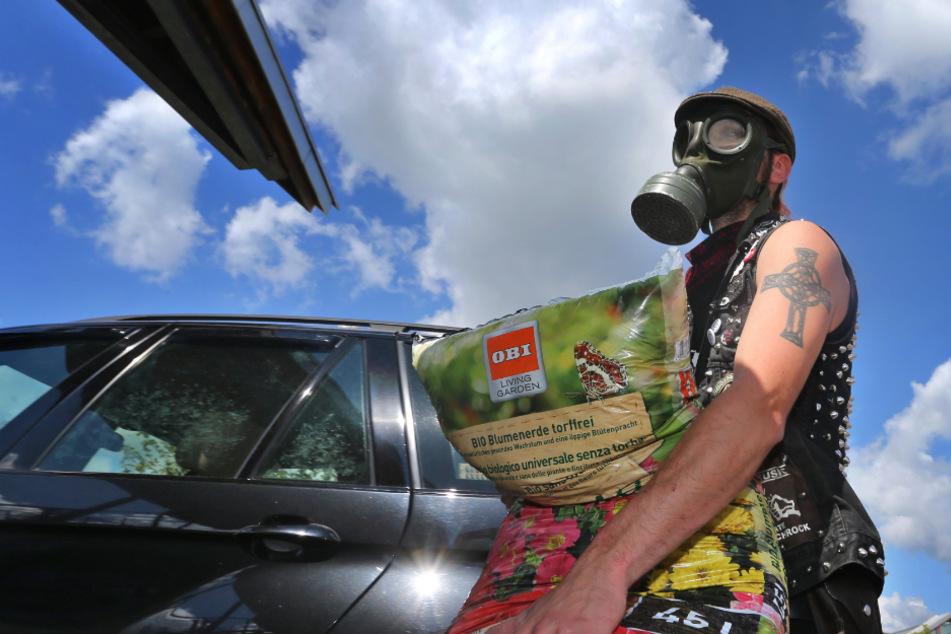 Ein junger Mann, der eine Gasmaske trägt, lädt vor einem Baumarkt die gekaufte Blumenerde in sein Auto. (Symbolbild)