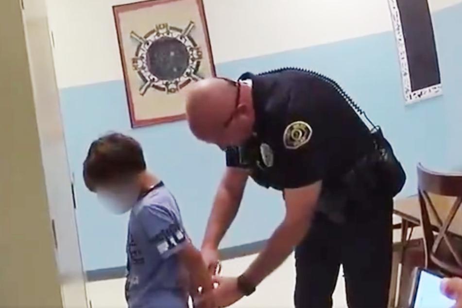 Ein Beamter nimmt den kleinen Jungen (1,09 Meter groß!) in der Schule fest.