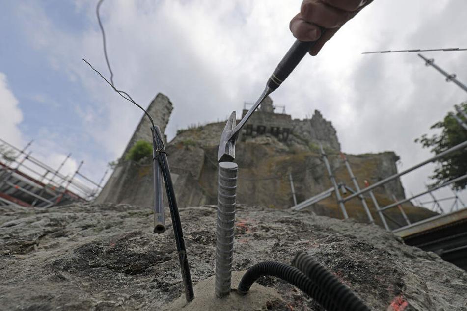 Arbeiter setzen unterhalb der Burgruine Anker, um einen Felssturz zu vermeiden.