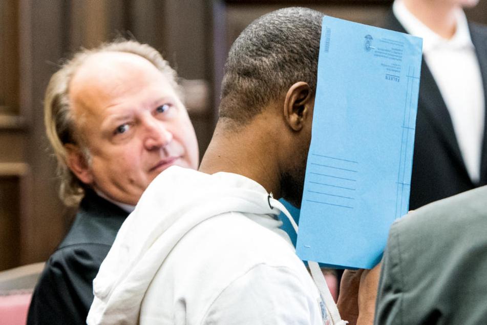 Im Gerichtssaal versteckt sich der Angeklagte hinter einer Mappe.