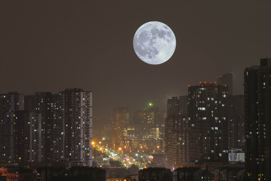 The moon rises above the skyscrapers of Nanjing.