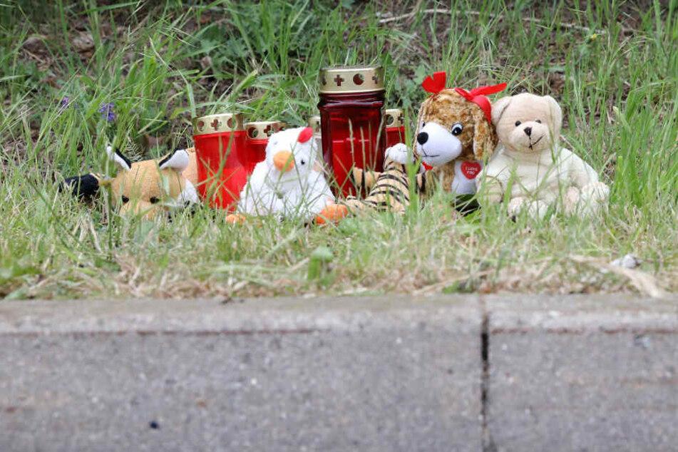 Blumen, Kerzen und Plüschtiere stehen an einer Stelle am Straßenrand im Stadtteil Lichtenhagen.