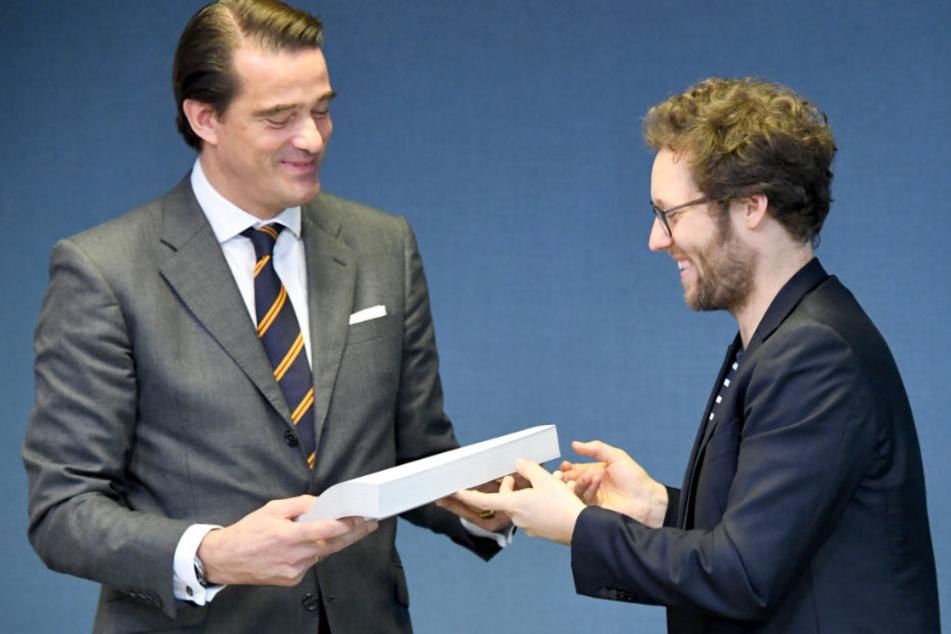 SH-Umweltminister Jan Philipp Albrecht (rechts) überreicht Pieter Wasmuth von Vattenfall die Genehmigung für den Abriss.