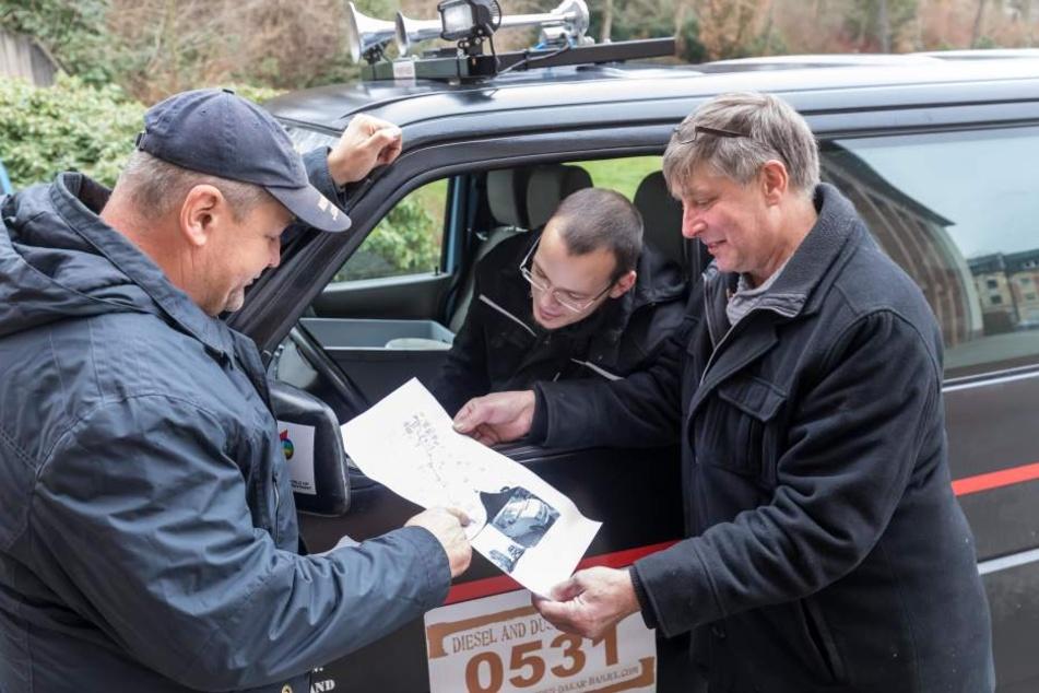 Holger (54) und Christian Wötzel (23) sowie Jochen Schmidt (57) studieren die Route der Rallye von Dresden nach Gambia.