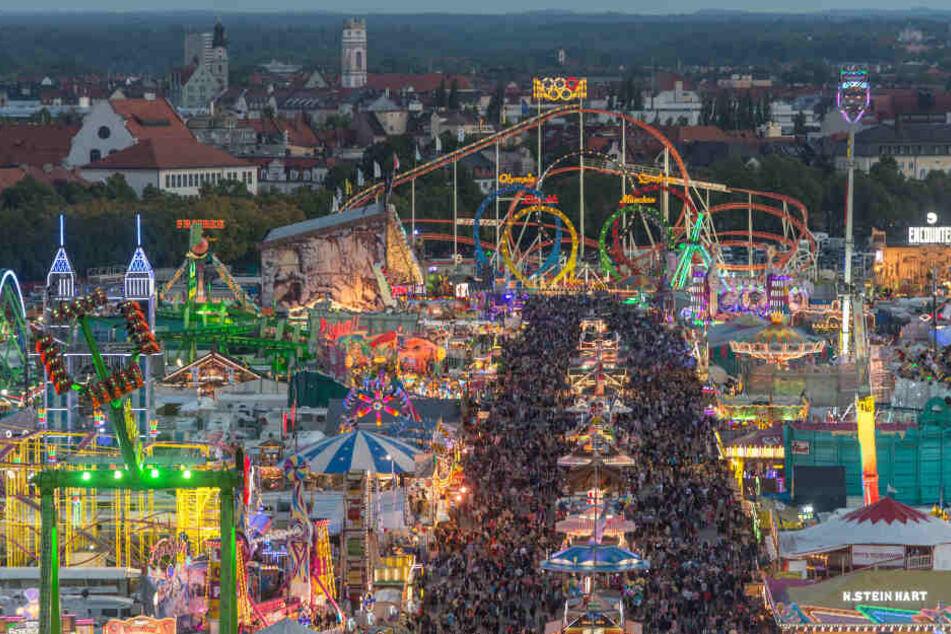 Zahlreiche Besucher sind zur blauen Stunde auf der Theresienwiese, dem Oktoberfestgelände, zu sehen.