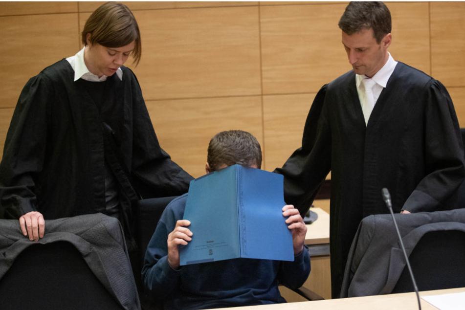 Der Angeklagte sitzt mit einer Mappe vor dem Gesicht im Gerichtssaal neben seinen Verteidigern, Christina Peterhanwahr und Henning Jansen.