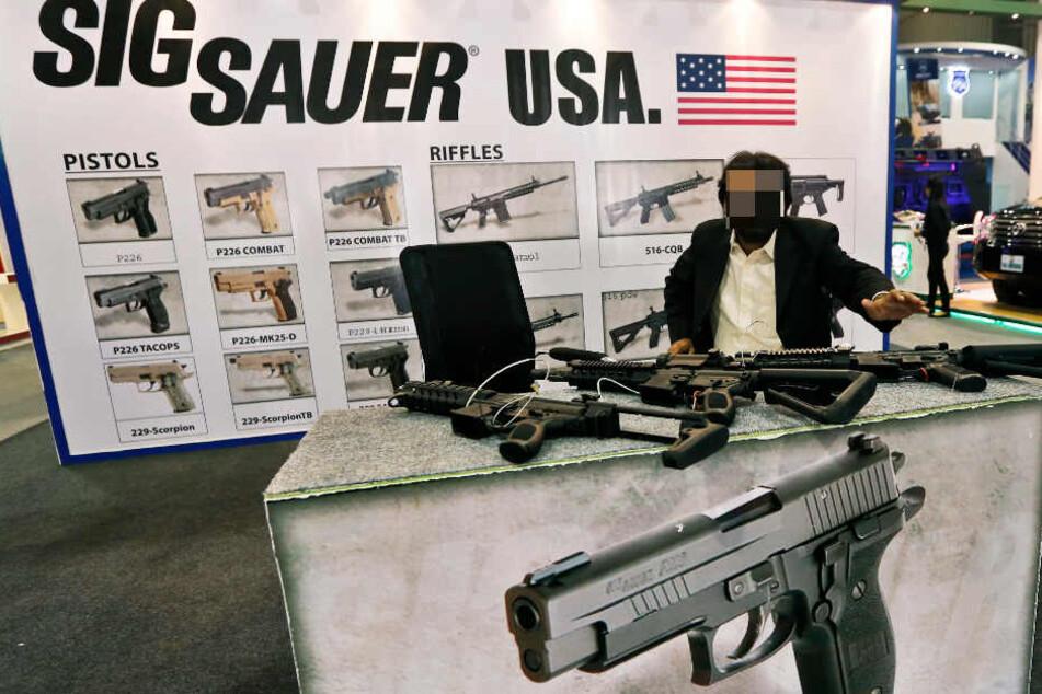 Ein Mann präsentiert auf einer Messe Waffen von Sig Sauer.
