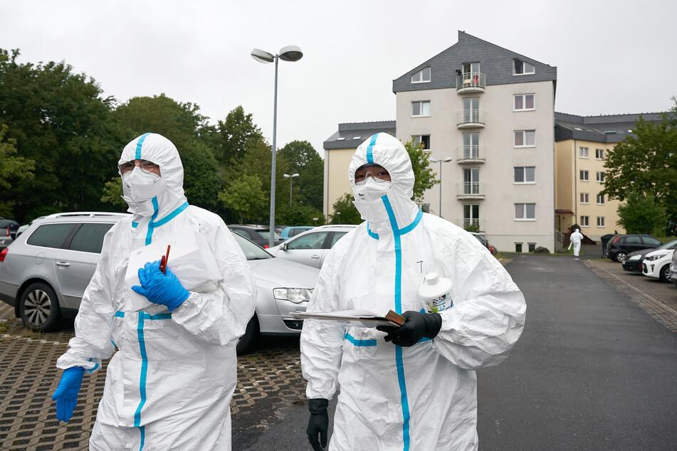 Einsatzkräfte in Schutzkleidung stehen vor einem der drei betroffenen Studentenwohnheime.