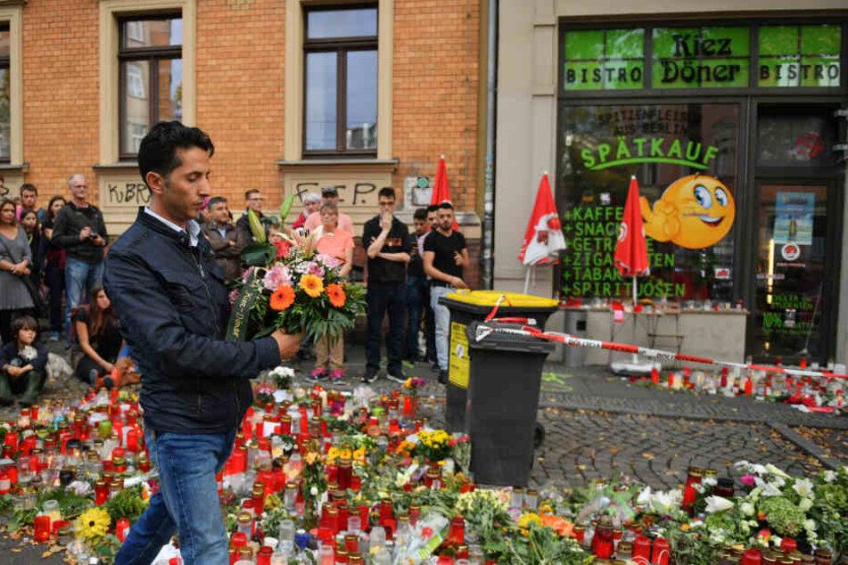 Ein Mitarbeiter des Kiez Döners legt Blumen am Gedenkort vor dem Imbiss ab.