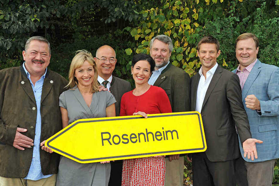 """Darsteller der """"Rosenheim Cops"""" vor dem entsprechenden Ortsschild."""