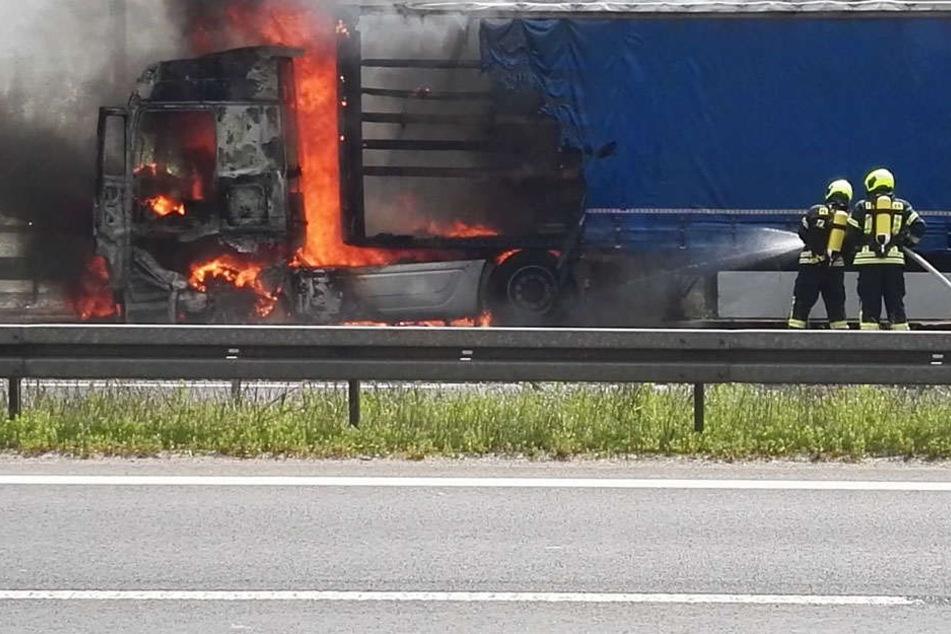 Kameraden der Feuerwehr löschen den Brand an dem Sattelzug.