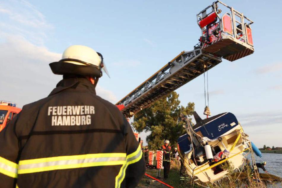 Das gekenterte Boot wird von der Feuerwehr aus der Elbe gehoben.