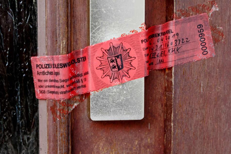 Ein Polizeisigel verschließt die Tür zur Wohnung der getöten Frau.