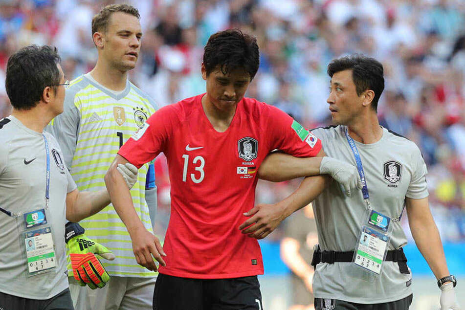 Ja-Cheol Koo (29, Mitte) musste verletzt behandelt werden. Im Hintergrund der deutsche Torhüter Manuel Neuer (32).