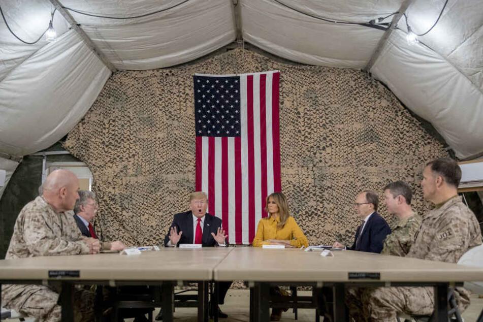 Donald Trump (Mitte l), Präsident der USA, First Lady Melania Trump und hochrangige Militärs bei einem Treffen auf dem Luftwaffenstützpunkt Al Asad. (Archivbild)