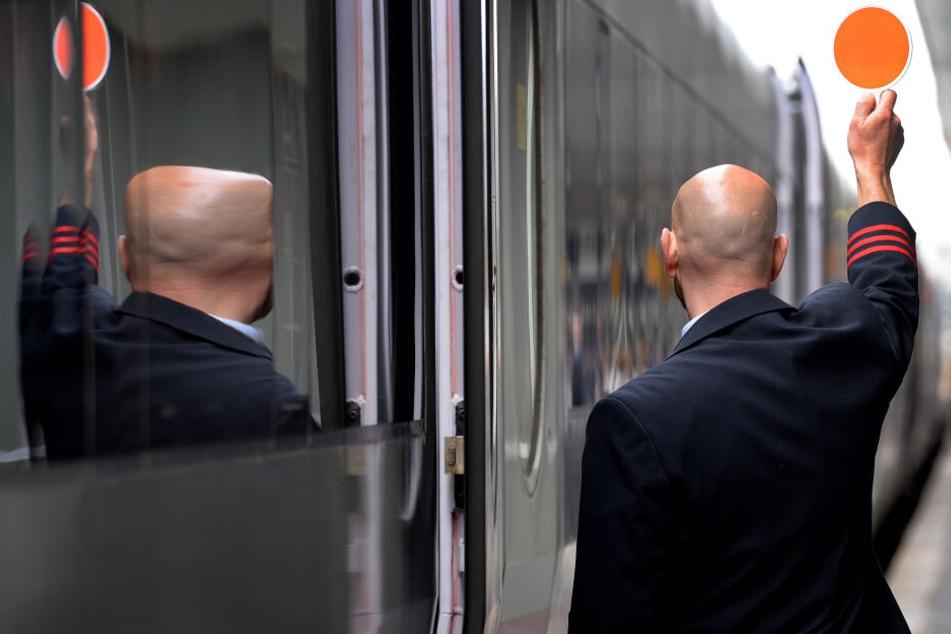 Ein Schaffner signalisiert dem Lokführer die Abfahrt.